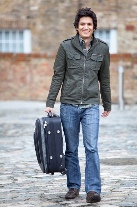 Man going on a trip carrying his suitcase and smiling