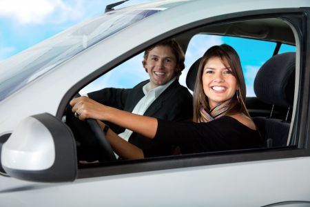 Happy couple driving a car and smiling