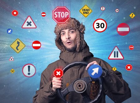Young man holding black steering wheel with road signs surrounding him