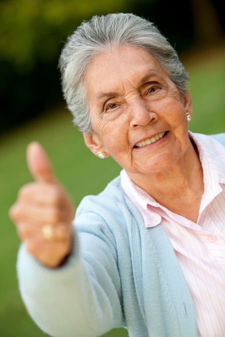 Lovely old woman with thumbs up and smiling outdoors