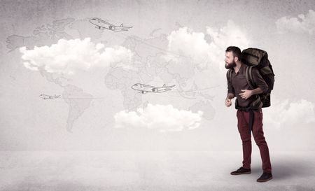Handsome young man standing with a backpack on his back and planes in front of a world map as a background
