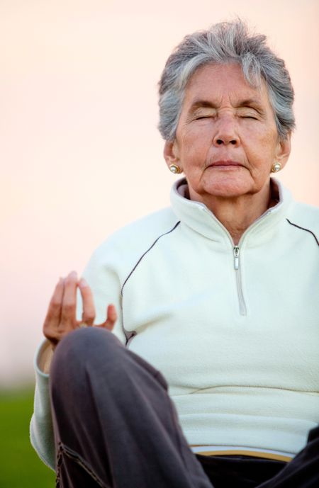 Elder woman doing yoga exercises outdoors - fitness concepts