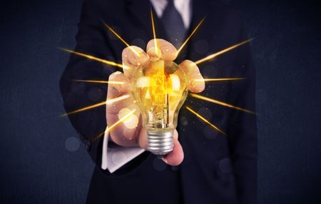 A male business person holding an electric light bulb in his hand with beam rays illustration concept.