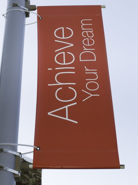Motivational banner on campus of community college: Achieve Your Dream