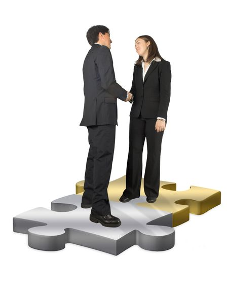 business couple handshaking over two puzzle pieces