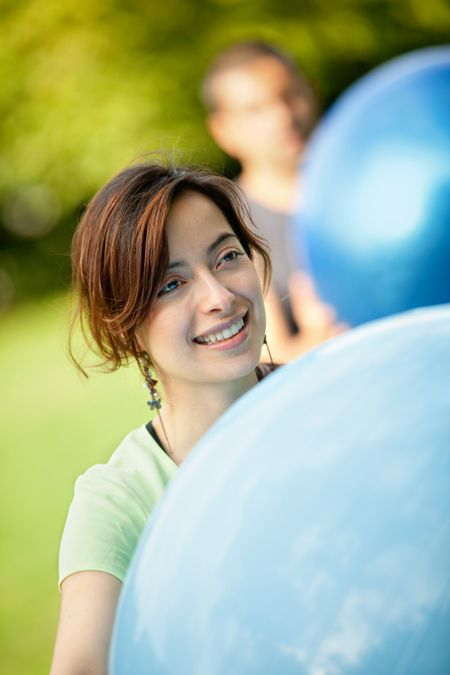 Beautiful woman portrait smiling holding a pilates ball outdoors