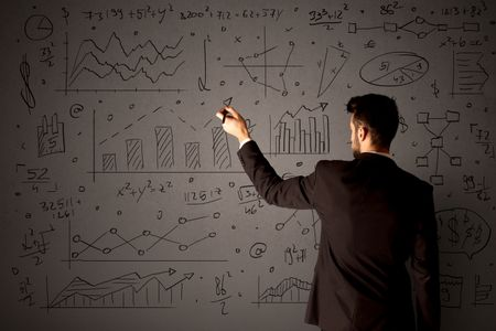 Young businessman in black suit standing in front of detailed calculations