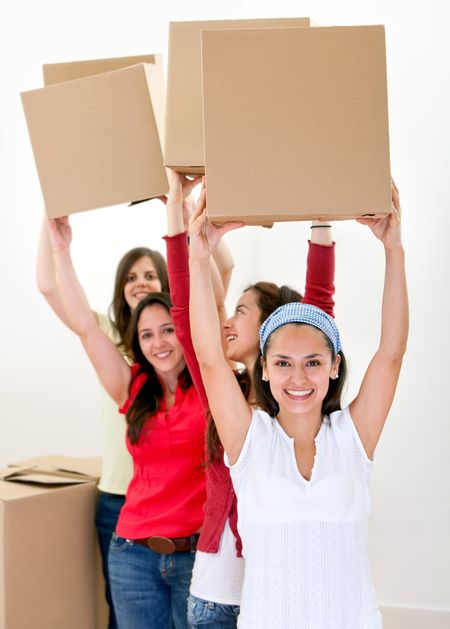 Happy group of women with cardboard boxes moving into a new house