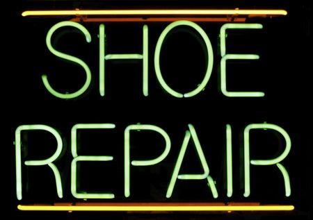 Neon sign in window of shoe repair shop