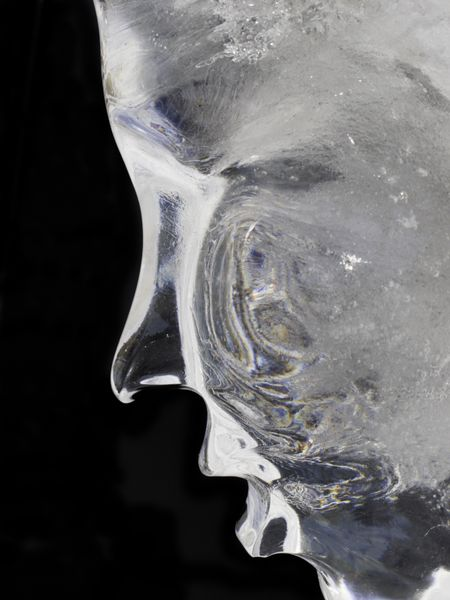 Profile of human face in ice (isolated on black)