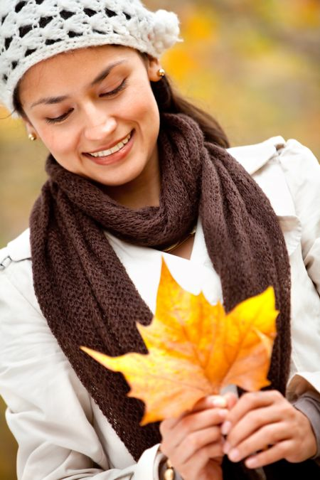 Autumn woman portrait holding a leaf and smiling