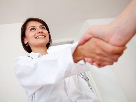 Female doctor handshaking a patient's hand and smiling