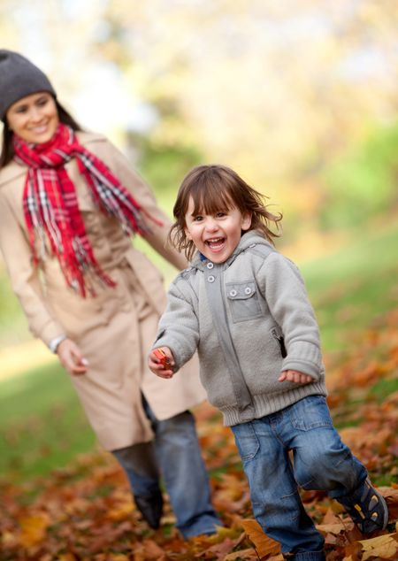 Mother and her son running at the park in autumn - family concepts