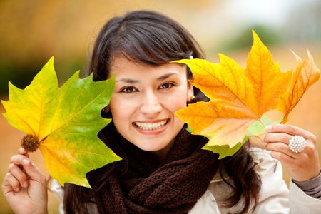 Portrait of an autumn woman holding leaves and smiling