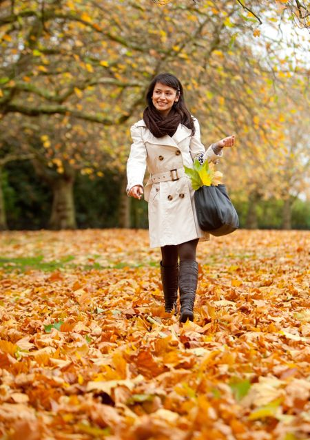 Autumn woman walking outdoors at the park