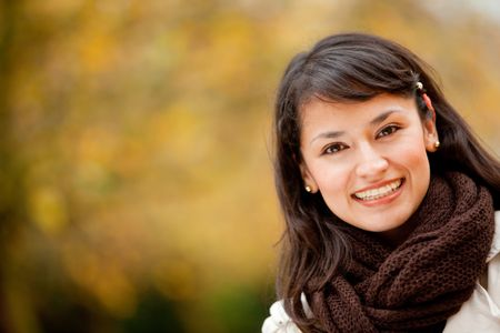 Portrait of an autumn woman smiling at the park