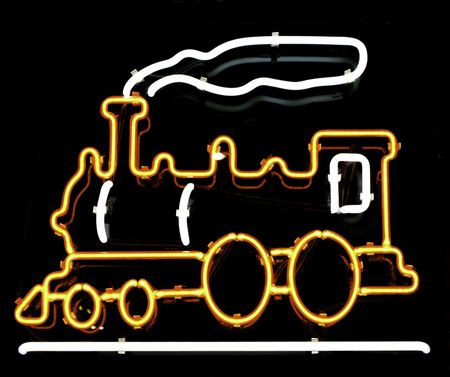 Neon sign of old-fashioned steam-powered locomotive and smoke in store window