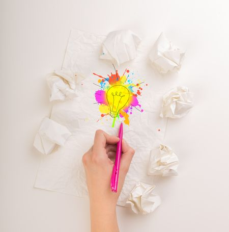 Female hand next to a few crumpled paper balls drawing a colorful lightbulb