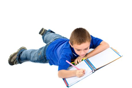 school boy doing homework on the floor isolated over a white background
