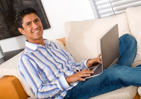 casual entrepreneur working from home looking very relaxed in his sofa browsing the web in his laptop computer