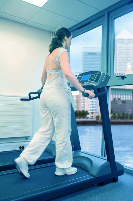 beautiful woman running on a treadmil dressed in white