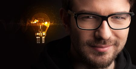 Portrait of a young businessman with a lightbulb next to him on a dark background