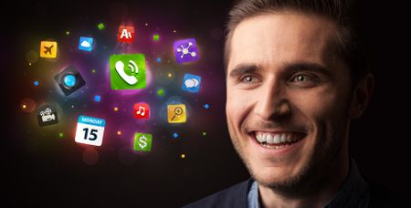 Portrait of a young businessman with colorful applications next to him on a dark background