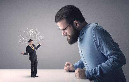 Young professional businessman being angry with an other miniature businessman who has scribbles above his head