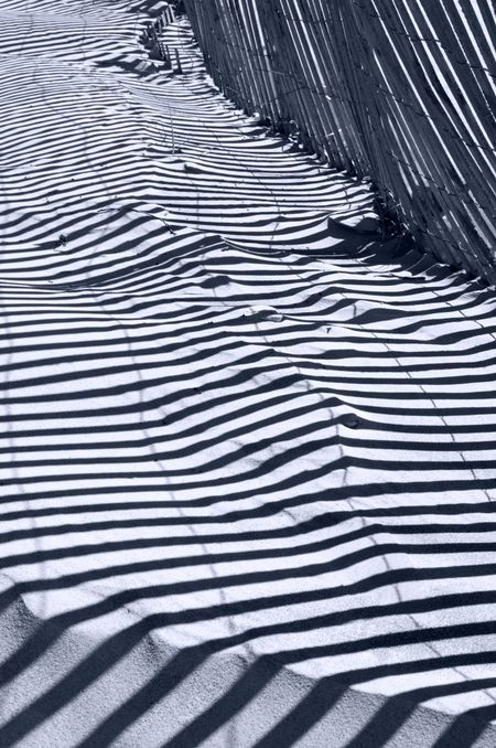 Pattern of shadows of beach fence on sand