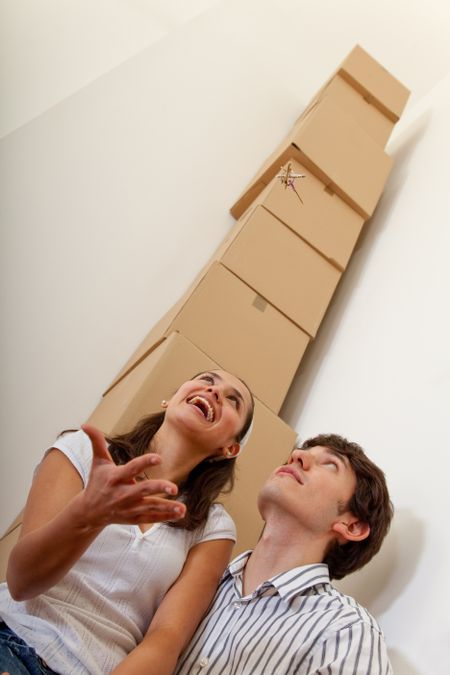 Couple with a pile of cardboard boxes from packing
