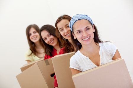 Group of girls with cardboard boxes moving into a new house.