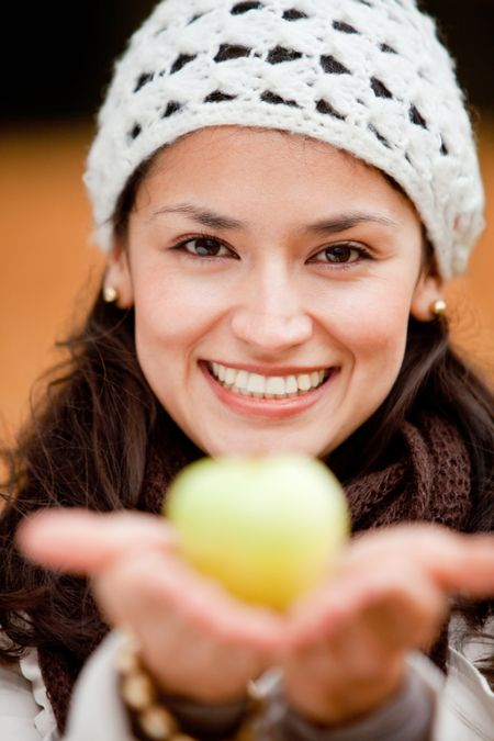 Beautiful autumn woman holding an apple and smiling