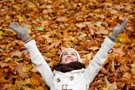 Happy autumn woman lying over leaves and smiling