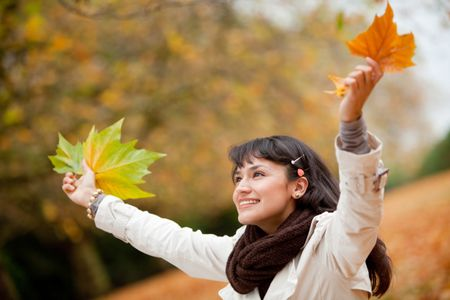 Autumn woman portrait smiling outdoors holding leaves
