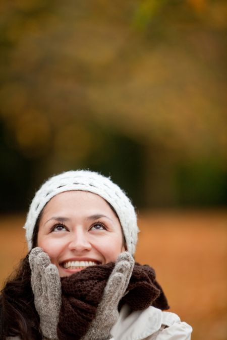 Happy autumn woman smiling at the park