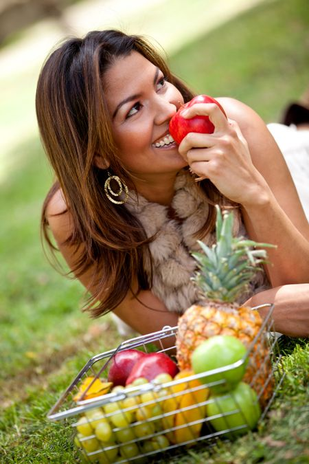 Healthy eating woman with a basket of fruits ? outdoors