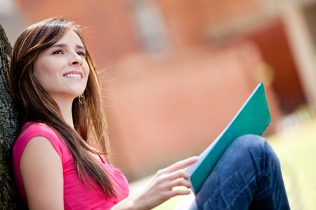 Thoughtful female student sitting outdoors and smiling