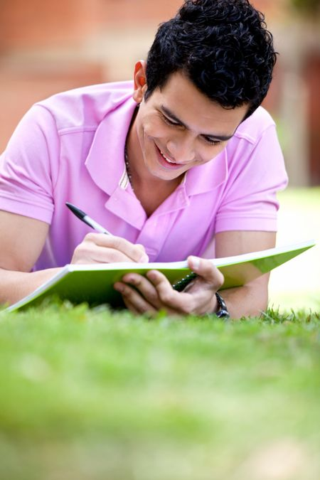 Casual guy studying outdoors lying on the floor