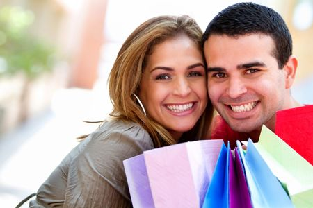 Happy couple at the shopping center with bags