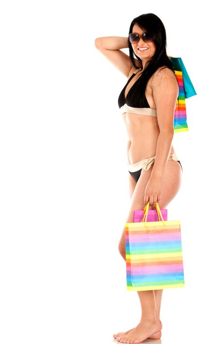 Beautiful shopping woman in a bikini smiling  - isolated over white
