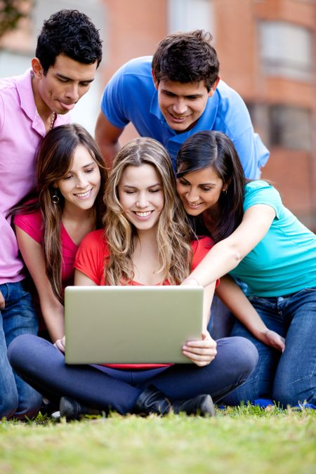 Surprised group of friends looking at a laptop outdoors