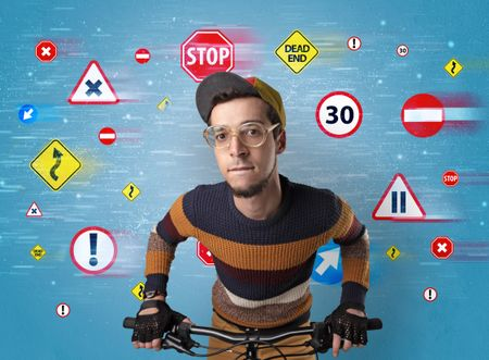 Young guy with stylish outlook and highway code on the background