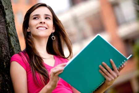 Pensive female student with a notebook outdoors