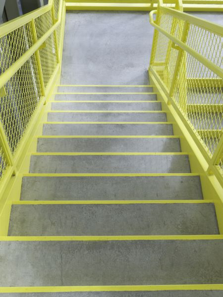 Staircase with yellow-edged steps and yellow sides in stairwell of community college