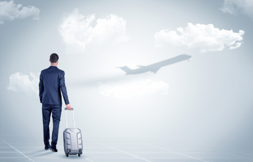 Young businessman with luggage walking towards an looking to a raising airplane