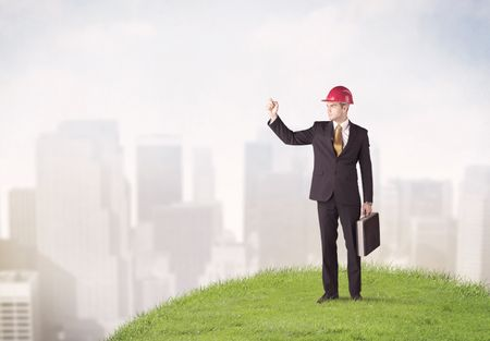 A cheerful caucasian elegant construction manager standing in small green grass and drawing with a pen in front of faded city landscape, tall buildings concept.