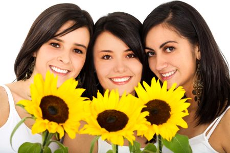Beautiful female friends holding sunflowers and smiling over a white background