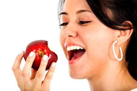Beautiful casual woman about to bit an apple smiling and isolated over a white background