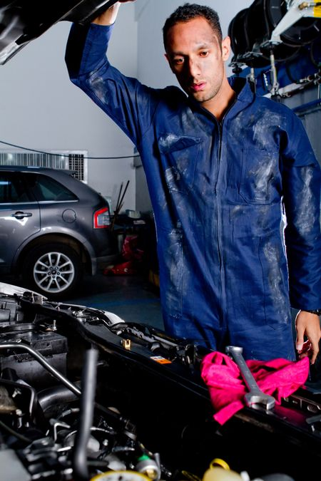 Mechanic fixing poping the hood of a car at the garage