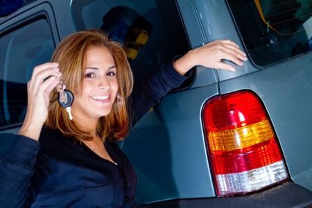 Woman holding the keys to her car and smiling